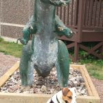 dinosaur statue looms above dog sitting in front of Fundy Geological Museum in Parrsboro, Nova Scotia