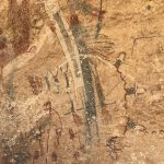 Prehistoric rock art depicting two shamans amid numerous other pictographs