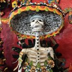 A decorated statue of a skeleton wearing a sombrero and a flowered corset