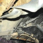 Crumpled liner of a wheel well on a trailer after a broken leaf spring