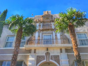 A view from Main Street looking upward toward the balcony above the front door of the historic Hotel Paisano. Palm trees on either side frame the portico.