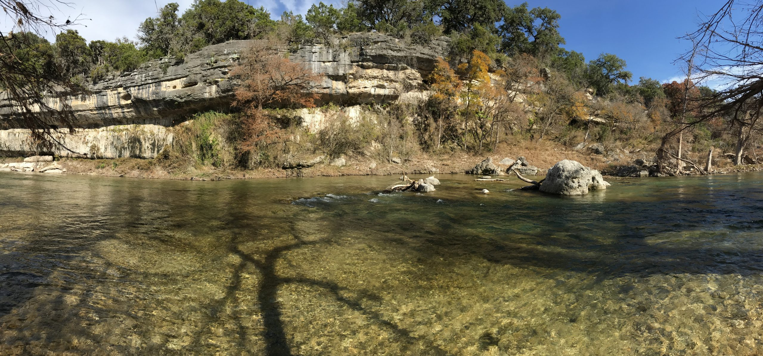 The clear water of the Guadalupe River runs next to a colorful sandstone cliff in Guadalupe River State Park